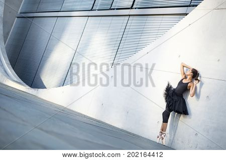 Delightful ballerina with closed eyes stands on the pointes and leans on the textured concrete wall of the modern building outdoors. She wears a black dance wear with a tutu and light ballet shoes.