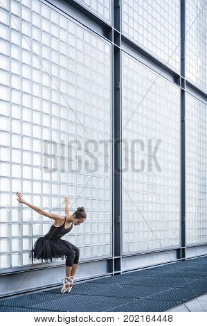 Charming ballerina stands on the toes with bended knees and holds her hands on the textured wall behind outdoors. She wears a black dance wear with a dark tutu and light ballet shoes. Vertical.