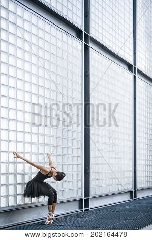 Attractive ballerina stands on the toes with bended knees and holds her hands on the textured wall behind outdoors. She wears a black dance wear with a dark tutu and light ballet shoes. Vertical.