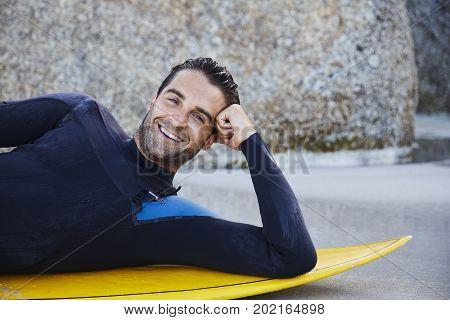 Surfer dude leaning on board on beach portrait