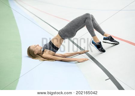 Athletic girl with closed eyes in gray sportswear does stretching exercise on the cycle track outdoors. She holds her feet on the toes and raises her pelvis while relies on the hands and shoulders.
