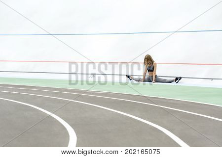 Beautiful girl sits on the twine on the cycle track outdoors. She holds her hands on the ground and looks downward. Girl wears a gray sportswear and dark sneakers. Horizontal.