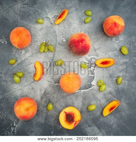 Peaches and grapes on dark background. Sliced peaches on dark table. Fruit concept. Flat lay, top view