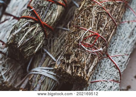 Top view of the bandaged branches of dried herbs: sage, wormwood, pine and juniper