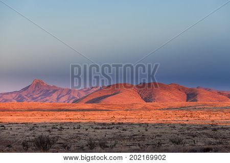 Sunset light on arid hills in barren high desert landscape of southern New Mexico NM USA