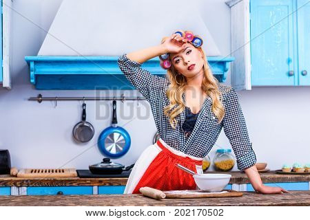 Tired Housewife Cooking In Kitchen