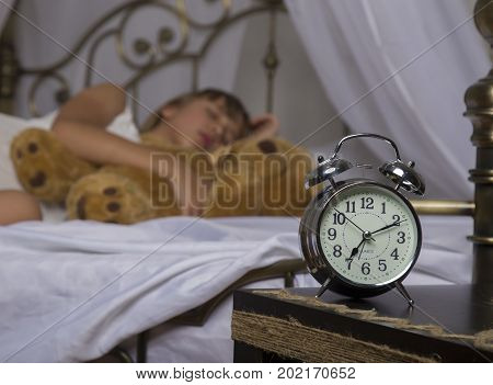 Early awakening. Alarm clock standing on bedside table. Wake up of an asleep young girl holding teddy bear in bed on a background.