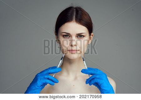 Beautiful young woman on white isolated background holds a syringe, plastic, medicine.
