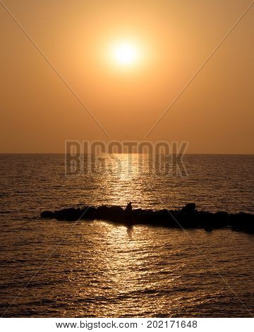 Vertical shot of the quiet summer sunset on the sea, the sun is reflecting in the water and illuminating the silhouette of a man sitting on the breakwater