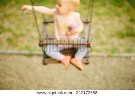 Happy baby playing with the swing blured photo concept