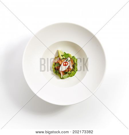 Menu in Pan-Asian cuisine - Tartar from salmon with avocado cream cheese chili pepper and fresh greens in the white bowl. Top view