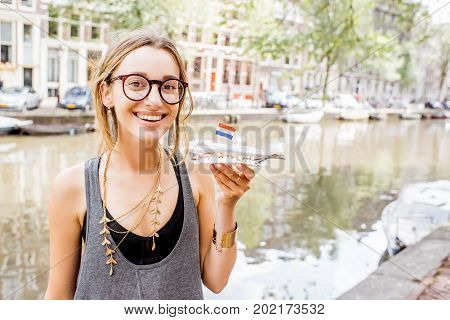 Young woman holding fresh harring standing outdoors in Amsterdam city. Harring with onion is a traditional dutch snack