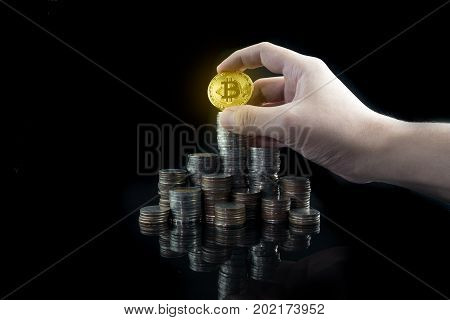 Pile of stacking coins with shiny golden bitcoin on top with grabbing hand king of all coins most valuable coin rising currency concept