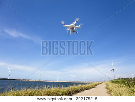 drone flying over the blue sky with wind turbine