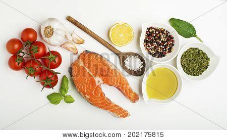 Raw steak of salmon with fresh ingredients on white background