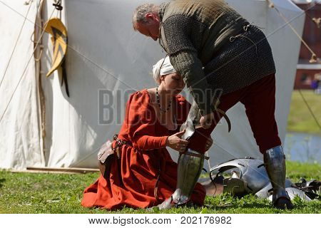 ST. PETERSBURG, RUSSIA - JULY 8, 2017: Participant of armored knight tournament preparing to the battle during the military history project Battle On Neva at St. Peter and Paul fortress