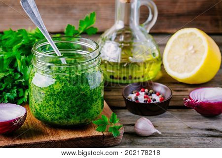 Traditional Green Chimichurri Sauce With Fresh Parsley, Red Onion, Garlic, Olive Oil In Glass