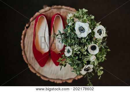 Shoes and flowers bouquet detail from a wedding with traditional theme.
