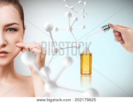 Cosmetic oil applying on woman face with pipette over molicules background. Beauty therapy concept.