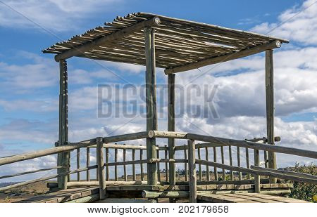 Close up of emply outdoor wooden pole tower on childrens recreational jungle gym against blue cloudy sky