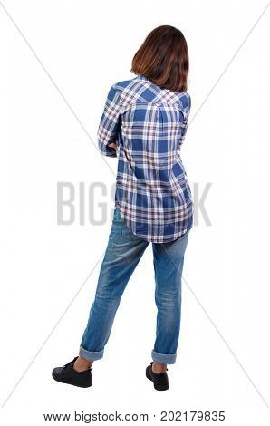 back view of standing young beautiful  woman.  girl  watching. Rear view people collection.  backside view of person. A girl in a checkered shirt is standing with her arms crossed over her chest.