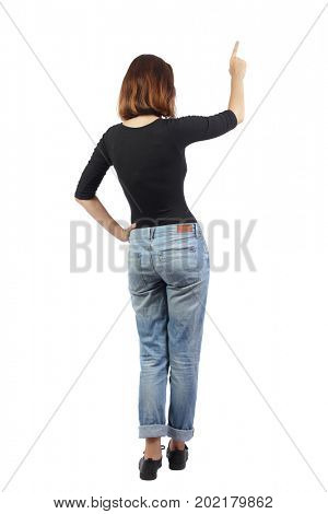 Back view pointing woman. beautiful girl. Rear view people collection.  backside view of person. girl in jeans and a black T-shirt is standing with her hand on her side and pointing with her finger up