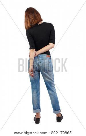 back view of standing young beautiful  woman. girl  watching. Rear view people collection.  backside view of person. girl in jeans and a black T-shirt is standing with her arms crossed behind her back