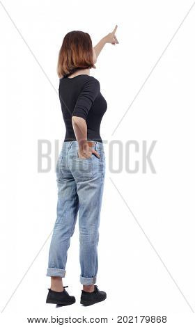 Back view pointing woman. Rear view people collection.  backside view of person. Isolated over white background. girl in jeans and a black T-shirt is standing with her hand in back pocket of her jeans