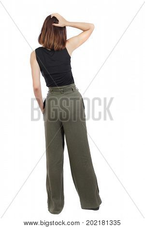 back view of standing young beautiful  woman.  girl  watching. Rear view people collection.  backside view of person. A top view of a girl in green stands rubbing her head thoughtfully