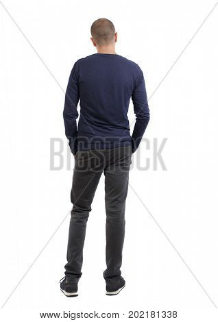 Back view man in trousers. Standing young guy. Rear view people collection.  backside view person. Isolated over white background. man in black pants and sneakers looks thoughtfully into the distance.