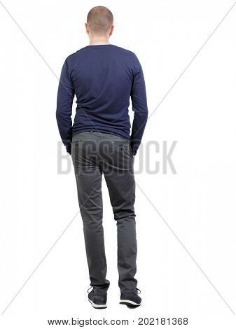 Back view of man in trousers. Standing young guy. Rear view people collection.  backside view of person.  Isolated over white background. A man in black pants and sneakers stands in a relaxed pose