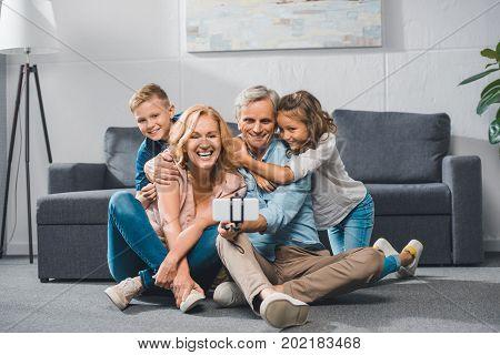 happy grandparents and grandchildren taking selfie on smartphone
