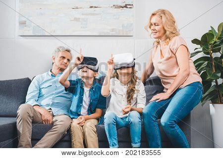 grandchildren using virtual reality headsets white grandparents sitting near at sofa