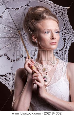 Beautiful woman in victorian style holding a lace umbrella. Luxury and elegance