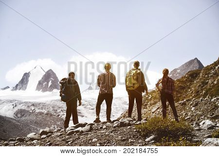 Group of four friends is looking on mountain's glacier. Trekking friends concept
