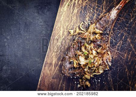 Barbecue dry aged Wagyu Tomahawk Steak as close-up on old wooden board