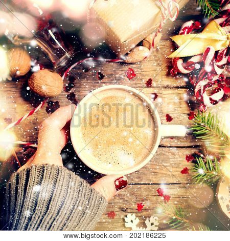 Hot Christmas Drinking Cocoa or Chocolate or Coffee in Small Cup Presents Boxes Cord Sparkles Fir Tree Branch Nuts on Wooden Background. Winter Time Top View Boke Effect