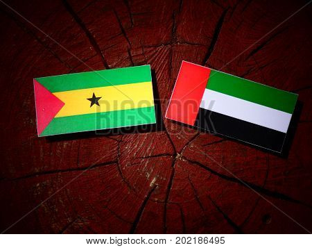 Sao Tome And Principe Flag With United Arab Emirates Flag On A Tree Stump Isolated