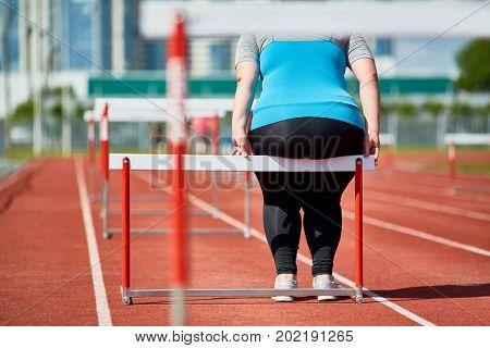 Fat woman in activewear sitting on hurdle on stadium