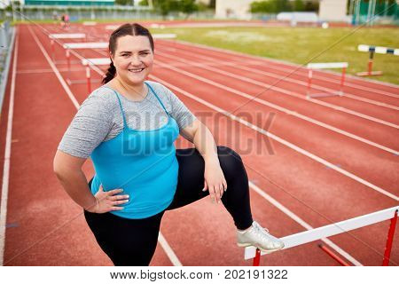 Successful overweight woman keeping one leg on hurdle while standing on racetrack