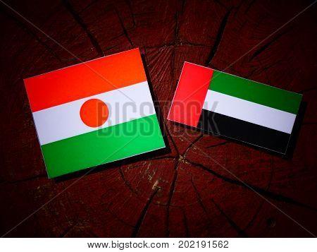Niger Flag With United Arab Emirates Flag On A Tree Stump Isolated