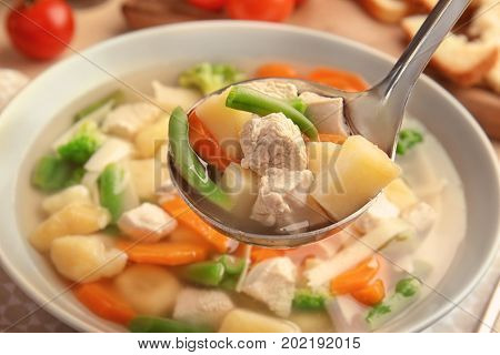 Ladle with turkey soup over plate, closeup