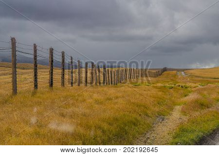 The boundary of a wooden fence with barbed wire in the field and clouds