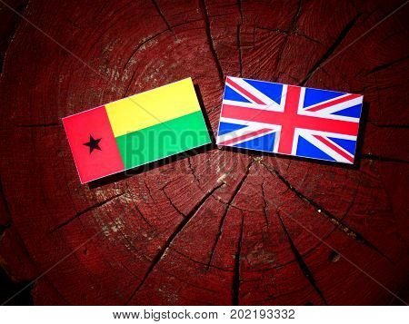 Guinea Bissau Flag With British Flag On A Tree Stump Isolated
