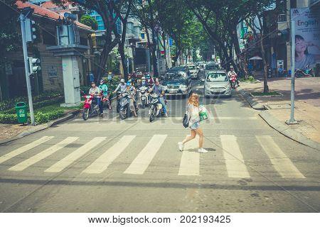 Ho Chi Minh City Vietnam : May 28: Unidentified Woman Walking Across Crosswalk On May 28 2017 In Ho Chi Minh City Vietnam.