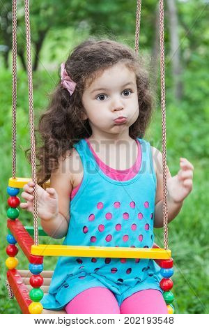 Happy baby girl making funny silly faces on a swing on summer day outdoors