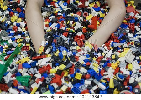 Children hands dig into pile of toys. Kid enfoy play a lot of playthings of constructor. Boy overwhelmed with colorful toys