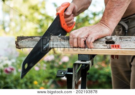 Caucasian man working cutting plank with handsaw outdoor in summer. Carpentry, construction.