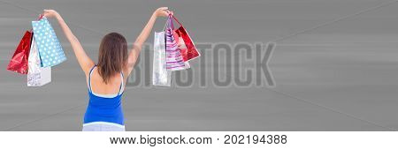 Digital composite of Back of shopper with bags in air against blurry grey background