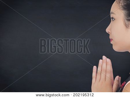 Digital composite of Side view of geisha hands together against navy chalkboard
